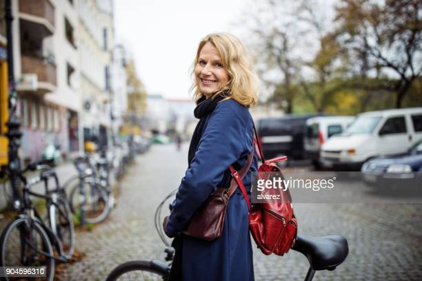 Smiling woman with bicycle in city during winter