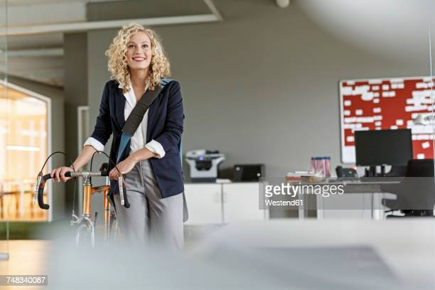 Smiling woman with bicycle in office