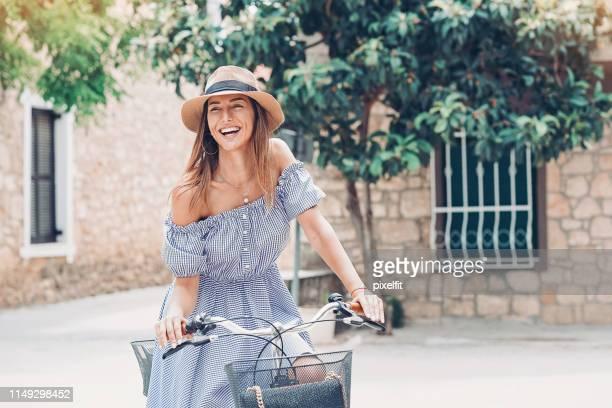 mulher de sorriso com a bicicleta em uma rua da cidade - vestido - fotografias e filmes do acervo