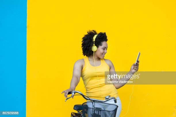 mulher sorridente com bicicleta usando telefone inteligente - primavera estação do ano - fotografias e filmes do acervo