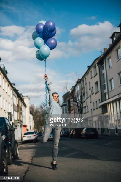 smiling woman with blue balloons on the street - standing on one leg stock pictures, royalty-free photos & images
