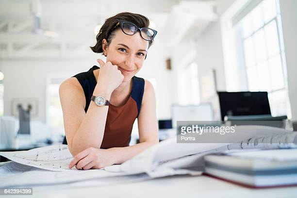 Smiling woman with blueprints in office