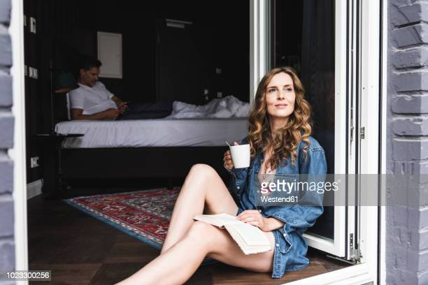 smiling woman with book and cup of coffee sitting at french window with man in background - woman sitting on man's lap stock pictures, royalty-free photos & images