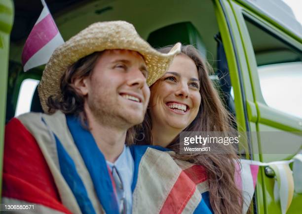 smiling woman with boyfriend in camper van looking away - insignia stock pictures, royalty-free photos & images