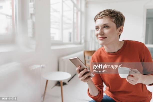 smiling woman with cell phone and espresso cup - mujeres de mediana edad fotografías e imágenes de stock