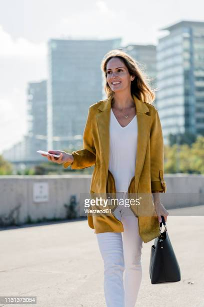 smiling woman with cell phone and handbag in the city on the go - yellow coat stock pictures, royalty-free photos & images