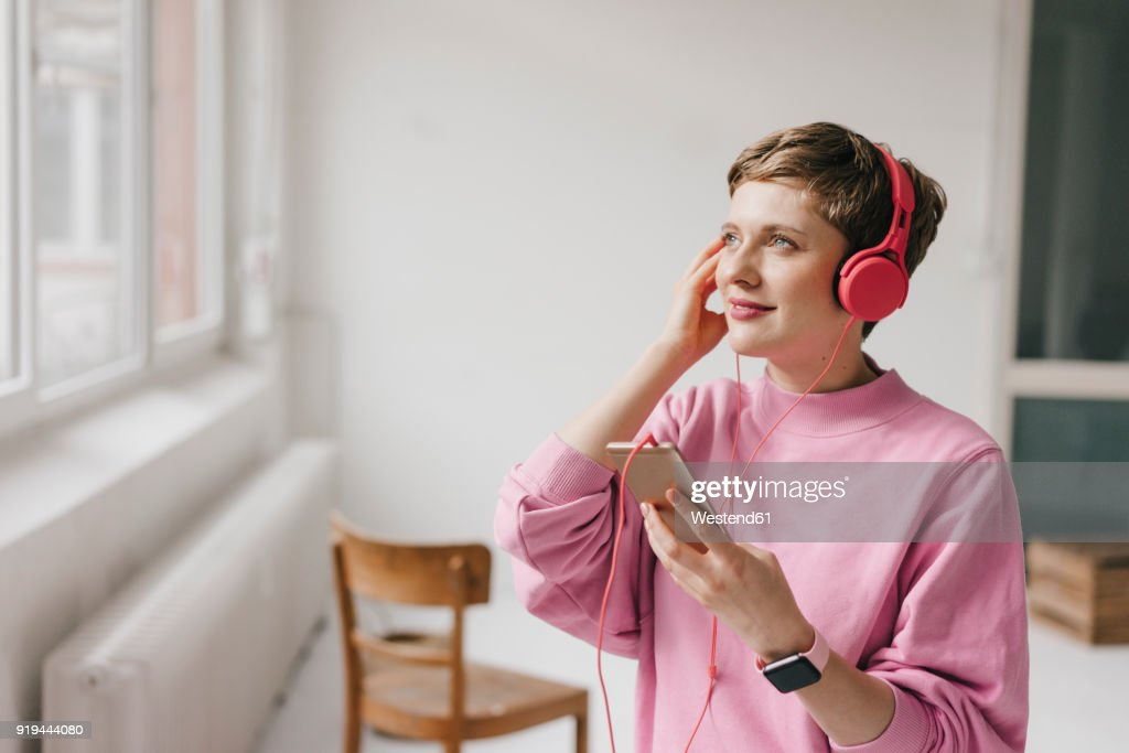 Smiling woman with cell phone and headphones listening to music : Stock-Foto