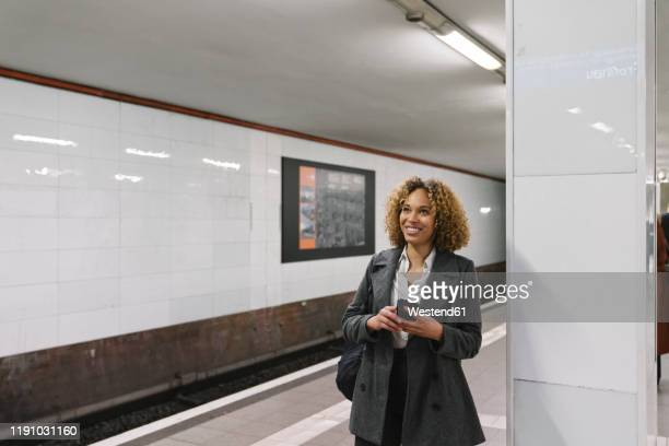 smiling woman with cell phone waiting in subway station - underground station stock pictures, royalty-free photos & images