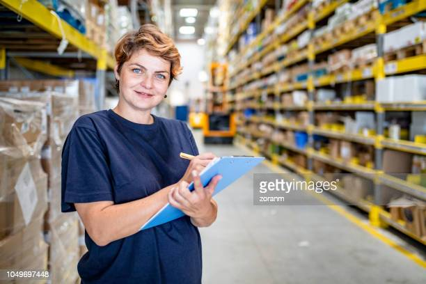 smiling woman with checklist working in warehouse - megastore stock photos and pictures