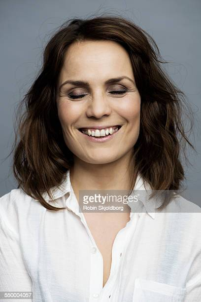 smiling woman with closed eyes in white shirt - femmes d'âge moyen photos et images de collection
