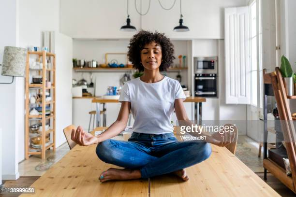smiling woman with closed eyes in yoga pose on table at home - spiritualiteit stockfoto's en -beelden