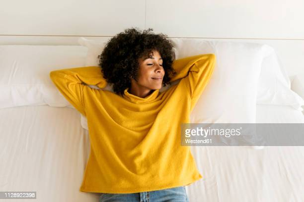 smiling woman with closed eyes lying on bed - deitar - fotografias e filmes do acervo