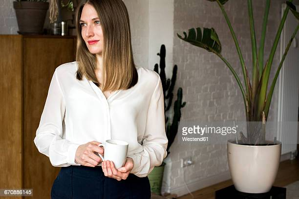 Smiling woman with coffee mug at home
