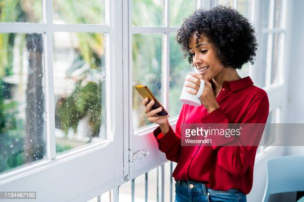 smiling woman with cup of coffee and cell phone standing at the window at home - black blouse stock pictures, royalty-free photos & images