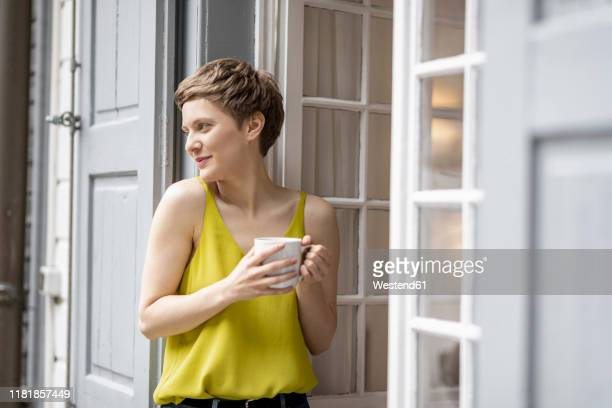 smiling woman with cup of coffee at the terrace door - capelli corti foto e immagini stock