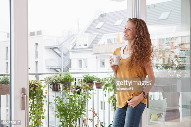 Smiling woman with cup of coffee leaning against balcony door
