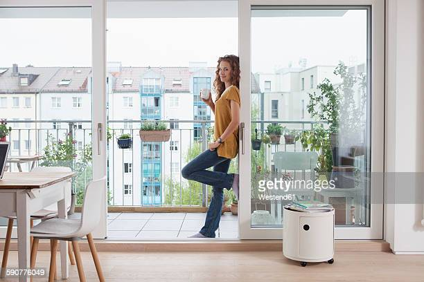 smiling woman with cup of coffee leaning against balcony door - lehnend stock-fotos und bilder