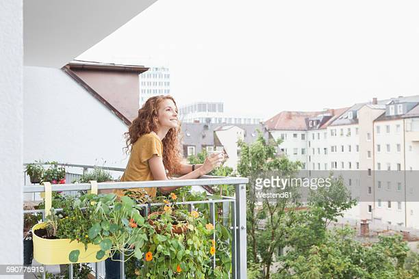 smiling woman with cup of coffee on balcony - バルコニー ストックフォトと画像