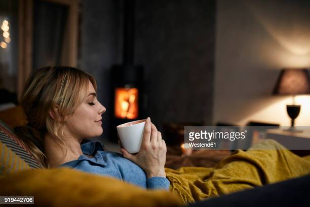 smiling woman with cup of coffee relaxing on couch at home in the evening - comfortabel stockfoto's en -beelden