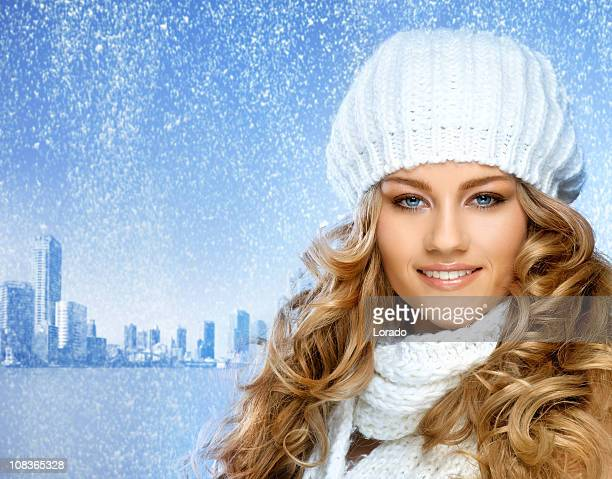 smiling woman with curled blond hair against city background