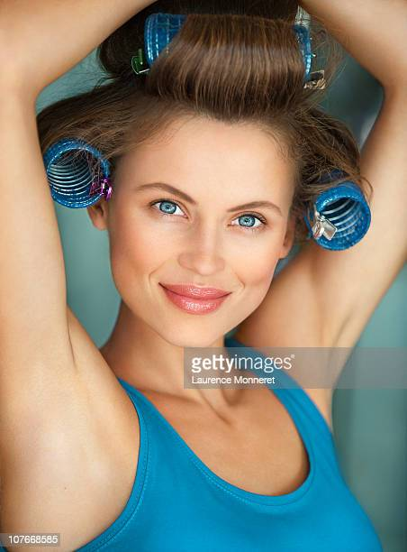 Smiling woman with curlers raising arms