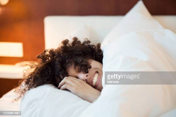 a smiling woman with dark curly hair in bed under the covers, head on a white pillow,. - bett stock-fotos und bilder