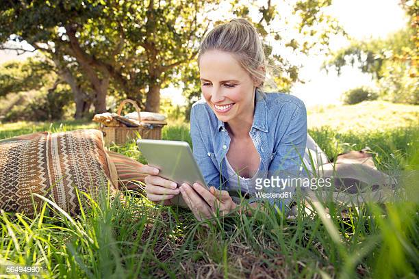 Smiling woman with digital tablet lying on meadow