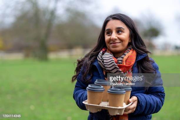 smiling woman with disposable coffee cups standing in park - mid adult women stock pictures, royalty-free photos & images