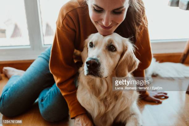 smiling woman with dog sitting on floor at home - golden retriever photos et images de collection
