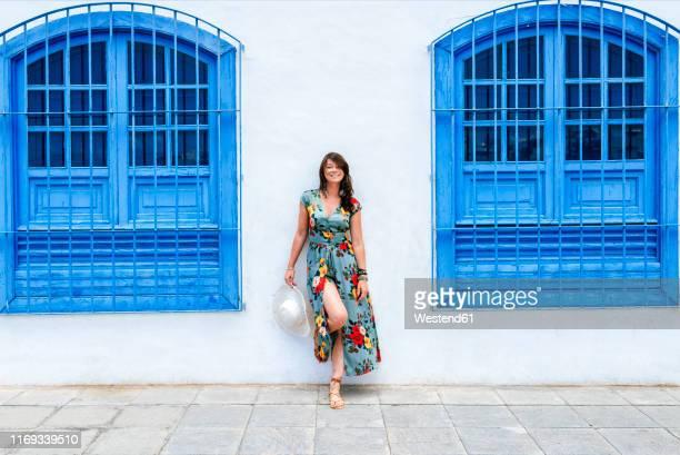 smiling woman with dress among blue windows - サンドレス ストックフォトと画像