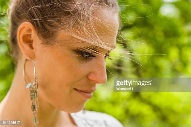 Smiling woman with earring outdoors