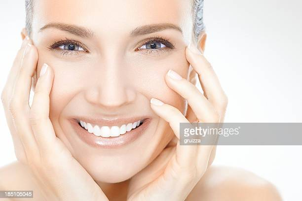 Smiling woman with face in hands