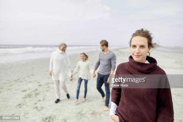 Smiling woman with family in background on the beach