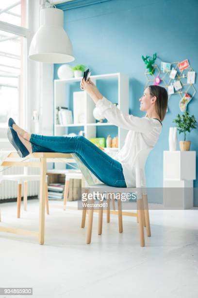 Smiling woman with feet up taking selfie in a loft