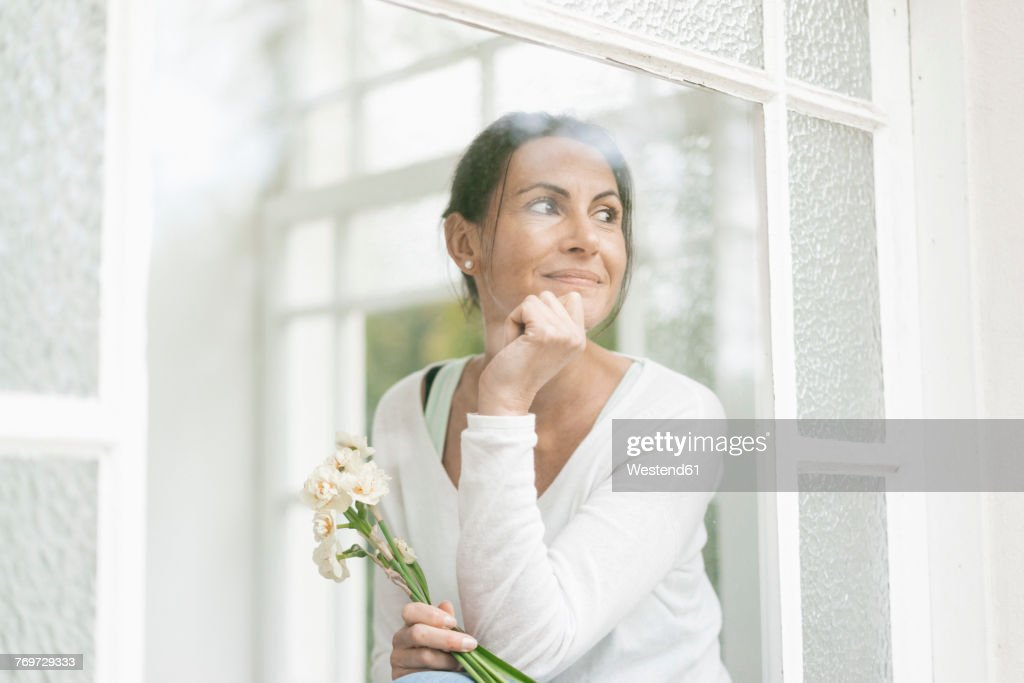 Smiling woman with flowers out of window : Stock Photo