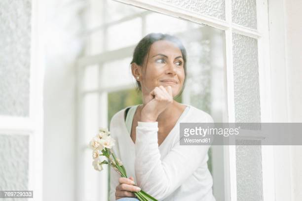 Smiling woman with flowers out of window