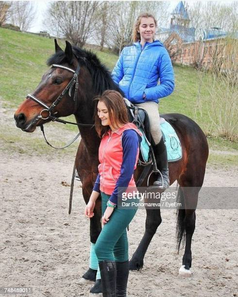 Smiling Woman With Friend Riding Horse By Field