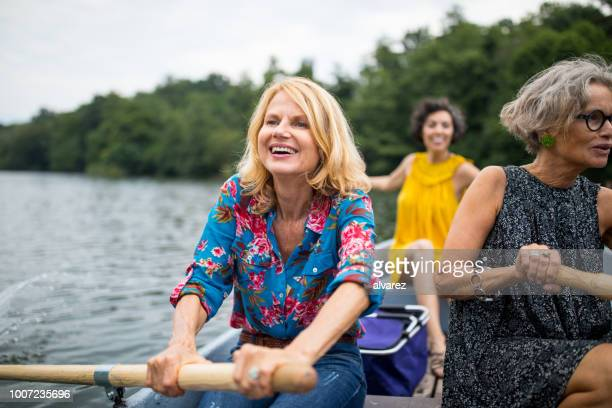 smiling woman with friend rowing boat in lake - rowing boat stock pictures, royalty-free photos & images