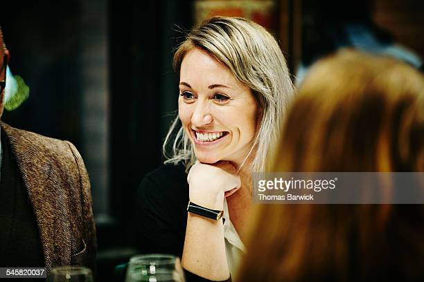 Smiling woman with friends at dinner party