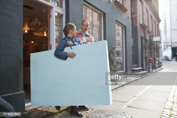 smiling woman with girl carrying large shopping bag outside store - oversized stock pictures, royalty-free photos & images