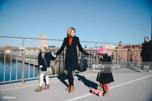 Smiling woman with girl looking at daughter riding push scooter on bridge in city against clear blue sky