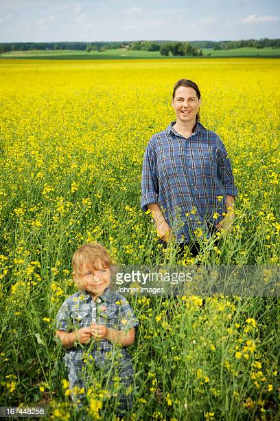 Smiling woman with girl on oilseed rape field