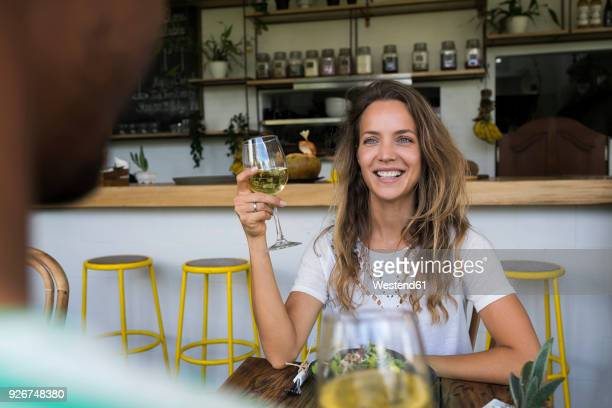 smiling woman with glass of wine looking at man in a cafe - daten stockfoto's en -beelden