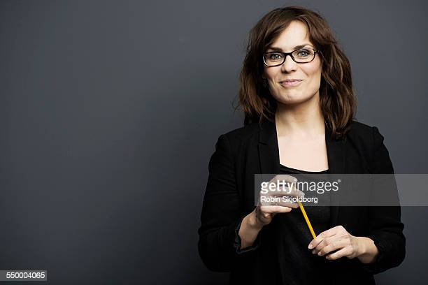 smiling woman with glasses holding pencil - waist up stock pictures, royalty-free photos & images