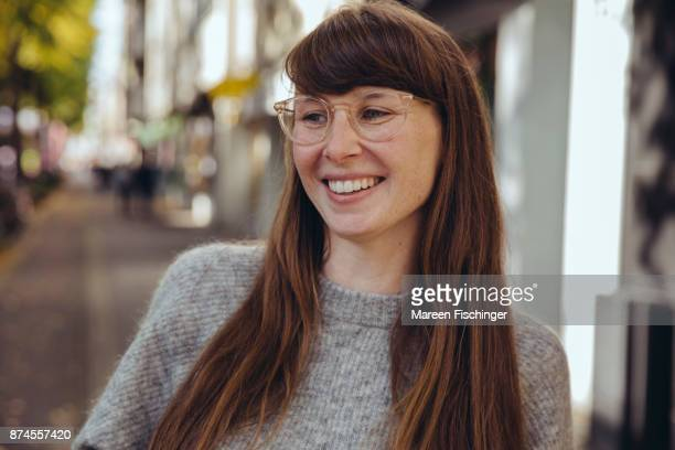 Smiling woman with glasses laughing outside wearing warm wool clothing