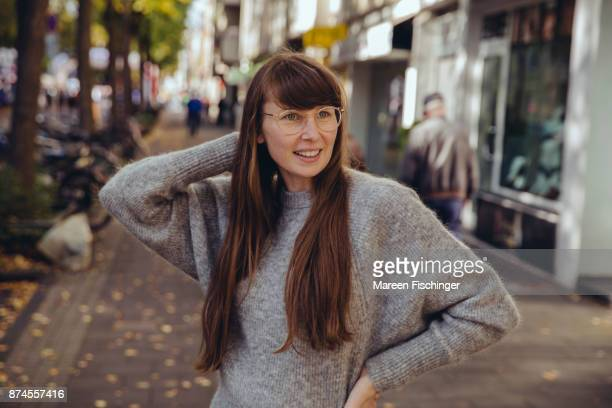 Smiling woman with glasses standing outside in warm wool clothing