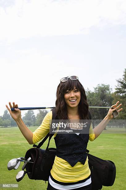 Smiling woman with golf clubs