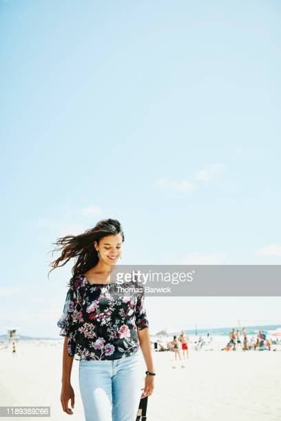 smiling woman with hair blowing in wind walking on wall by beach - light blue stock pictures, royalty-free photos & images