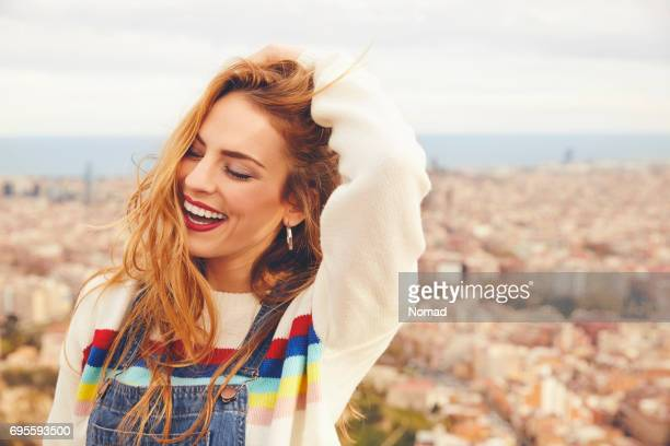 Smiling woman with hand in hair against cityscape