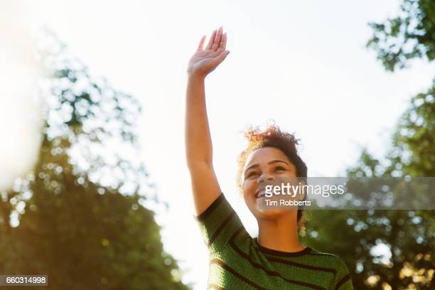 Smiling woman with hand in the air